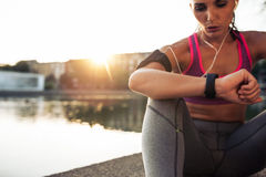 Runner checking her performance on fitness smart watch device. Beautiful young woman sitting outdoors using a smartwatch to monitor her progress. Caucasian Royalty Free Stock Image