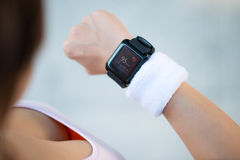 Runner checking pulse. Female runner checking pulse on her smart watch Royalty Free Stock Photos