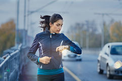 Runner checking time. Young fitness woman runner checking time from smart watch. Young woman checking heart rate while jogging on street at dusk. Young woman stock photography