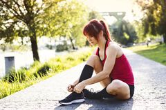 Runner in the city sitting on concrete path tying shoelaces. Young female runner in the city sitting on concrete path tying her shoelaces royalty free stock photos