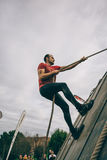 Runner climbing wall with a rope in test of extreme obstacle race Royalty Free Stock Images