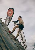 Runner climbing wall with a rope in test of extreme obstacle race Stock Photos