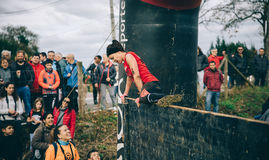 Runner climbing wall in a test of extreme obstacle race Stock Images