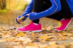 Runner. Close up of feet of a runner running in autumn leaves training exercise Stock Image