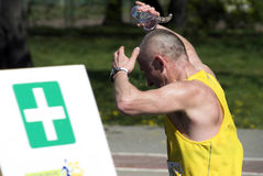 Runner cooling down. A hot runner cools down by pouring cold water over his head at a medical aid station on the course Royalty Free Stock Photo