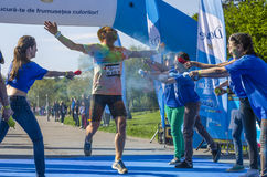 Runner covered with blue powder. Male runner enjoys being showered with blue powder by smiling girls at the Color Run event on April 26 in Bucharest, Romania Royalty Free Stock Photography