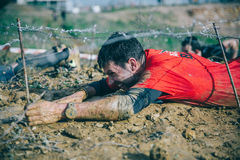 Runner crawling under barbed wire in a test of extreme obstacle race Royalty Free Stock Photos