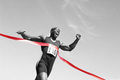 Runner Crossing Finish Line. Low angle view of an African American male runner crossing finish line against blue sky stock photo
