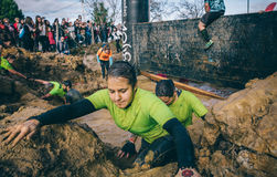 Runner crossing mud pit in a test of extreme obstacle race Royalty Free Stock Photography
