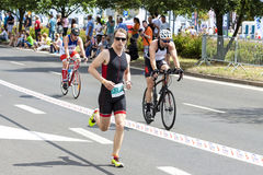 Runner and cyclists during first Triathlon Szczecin race. SZCZECIN, POLAND - JULY 06, 2014: Runner and cyclists during first Triathlon Szczecin race royalty free stock image