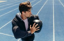 Athlete training with a medicine ball on running track Stock Images