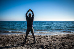 Runner doing stretching exercise on a beach Stock Photos