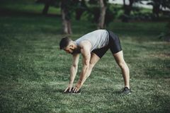Runner doing stretching exercise before jogging. Muscular man runner doing stretching exercise, preparing for morning workout in the park. Street fitness, sport Royalty Free Stock Images