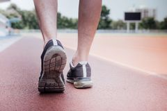 Runner feet of athlete running on road track, exercise jog workout wellness concept stock photography