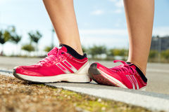 Runner feet preparing for running on road closeup on shoe. Royalty Free Stock Photography