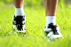Runner feet running on grass closeup on shoe Stock Images