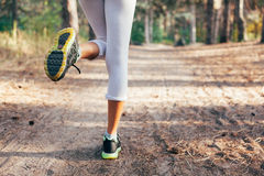 Runner feet running on road close-up on shoe. woman fitness Stock Photos