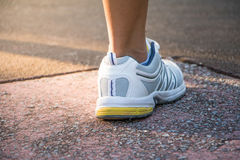 Runner feet running on road closeup on shoe. Royalty Free Stock Images