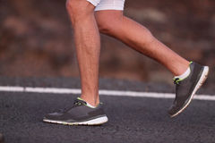 Runner feet running on road closeup on shoe Stock Photos