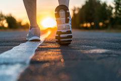 Runner feet running on road closeup. On shoe. man fitness sunet jog workout welness concept on sunrise Royalty Free Stock Photos