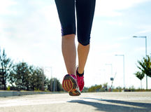 Runner feet running on road closeup on shoe. Royalty Free Stock Photos