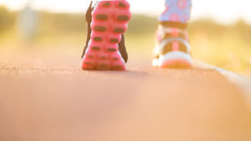 Runner feet running on road closeup on shoe. woman fitness sunri Royalty Free Stock Images