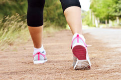 Runner feet running on road closeup on shoe. Woman fitness sunrise jog workout Stock Photo