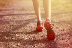 Runner feet running on road closeup on shoe. woman fitness sunrise jog workout welness concept. Runner feet running on road closeup on shoe. woman, fitness Stock Photo