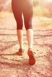 Runner feet running on road closeup on shoe. woman fitness sunrise jog workout welness concept. Runner feet running on road closeup on shoe. woman, fitness Royalty Free Stock Images