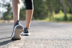 Runner feet running on road closeup on shoe. Woman fitness sunrise jog workout welness concept. Young fitness woman runner athlete. Running at road stock image