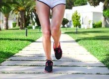 Runner feet running on road in the park. Woman fitness sunrise j Stock Images
