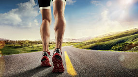 Runner feet running on road. Sports background. Runner feet running on road closeup on shoe Royalty Free Stock Images