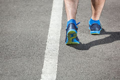 Runner feet running on stadium. Closeup on shoe - back view Royalty Free Stock Photos