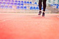 Runner feet running on stadium. Track closeup - woman running concept. Sunny Day Stock Photography