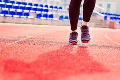 Runner feet running on stadium. Track closeup - woman running concept. Sunny Day Royalty Free Stock Image
