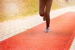 Runner feet running on stadium. Track closeup - woman running concept. Sunny Day Stock Image