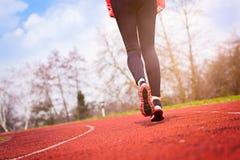 Runner feet running on stadium. Track closeup - woman running concept. Sunny Day Royalty Free Stock Photography