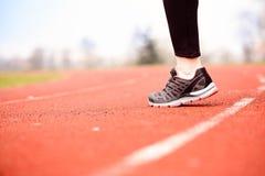 Runner feet running on stadium. Track closeup - woman running concept. Sunny Day Stock Images
