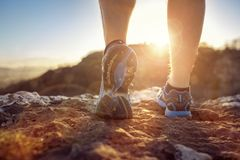 Runner feet running on trail looking at sunset stock photography