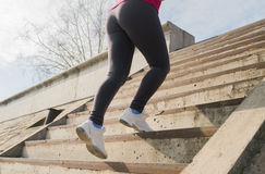 Runner feet running upstairs closeup on sneakers. Woman fitness sunrise jog workout welness concept Royalty Free Stock Photo