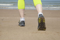 Runner feet on the sand beach. Closeup on shoe Stock Images
