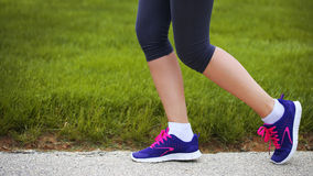 Runner Female Feet Running beside Green Grass. Jog Royalty Free Stock Image