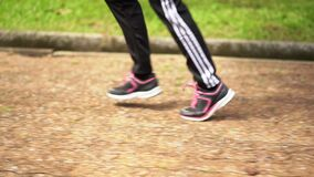 Runner female feet running in the park exercising outdoor