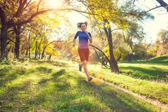 Woman trains in nature. Runner in flight phase. The girl runs through the autumn park. Slender woman trains in nature. Sports in the forest. Brunette runs along royalty free stock images