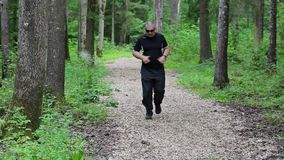 Runner on forest trails with epigastric pain. In summer day stock video