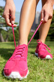 Runner getting ready tying running shoes laces. Runner getting ready for jogging tying running shoes laces - Woman preparing before run putting on trainers in stock photo