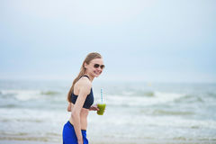 Runner girl drinking green vegetable smoothie Stock Photography