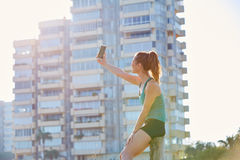 Runner girl having a rest shooting selfie. With smartphone outdoor building park Royalty Free Stock Photo