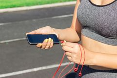 Runner girl holding smartphone and inserts headphones on the phone. Training in the morning time. People sport and fitness concept stock photos