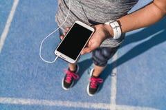 Runner girl phone screen music for running track. Runner girl holding smartphone using touchscreen for choosing music or texting sms on app before running on stock photos